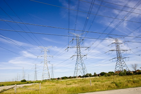Electricity towers in a field under blue sky